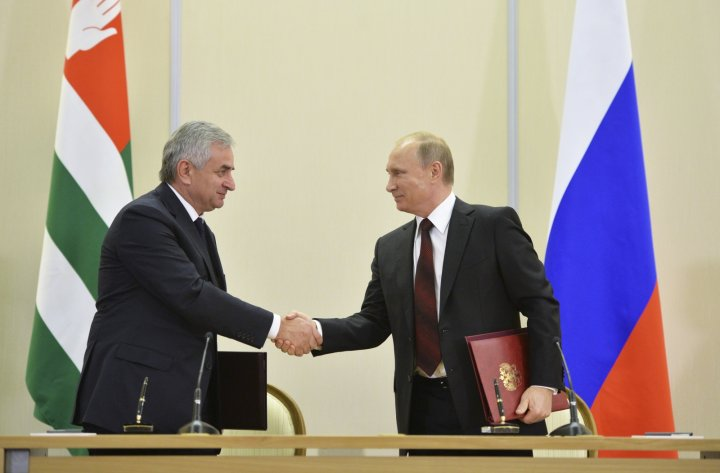 Russian President Vladimir Putin (R) shakes hands with Abkhazia's President Raul Khadzhimba during a signing ceremony at the Bocharov Ruchei state residence in Sochi