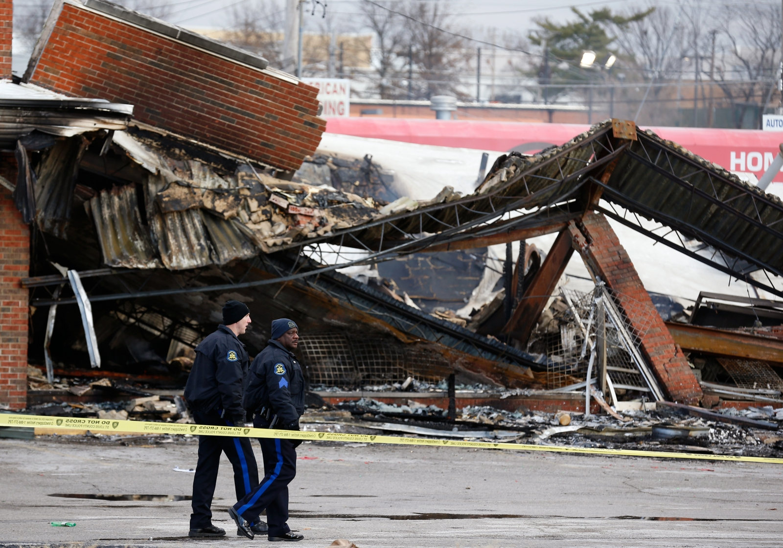 Police officers look over the site of a building that was burned during riots in Ferguson, Missouri