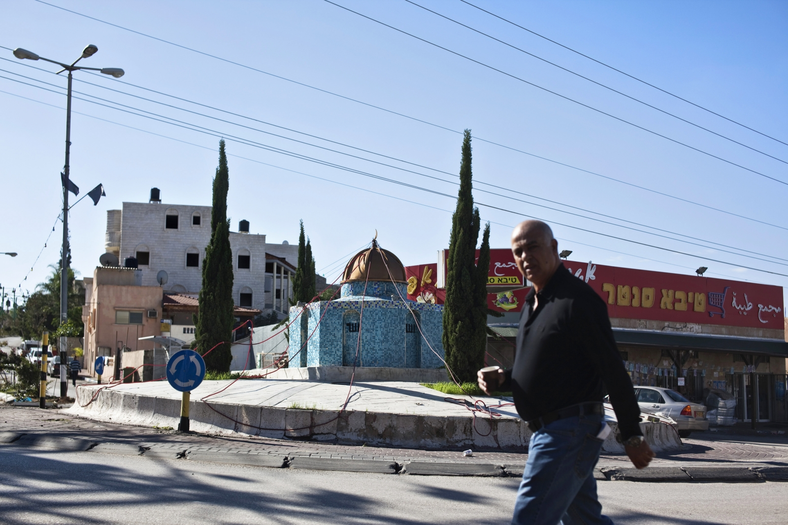 An Israeli Arab man walks past a replica of the Dome of the Rock mosque, in the Arab town of Kafr Qassem