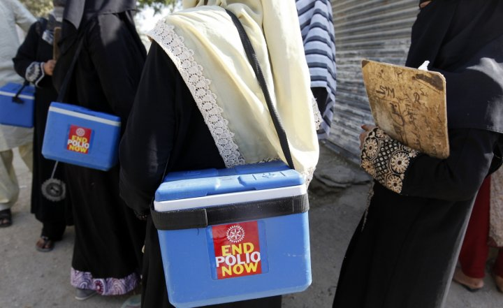Polio vaccinators carry boxes of polio vaccine drops as they head to the areas they have been appointed to administer the vaccine, in Karachi October 21, 2014.