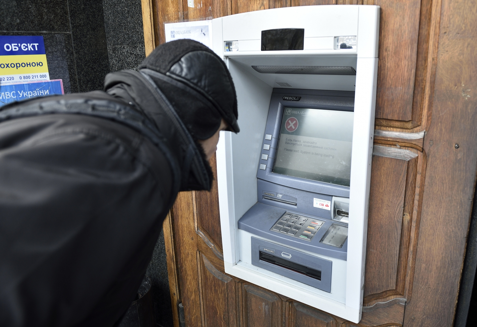 A man stands in front an ATM machine which is out of order, on November 26, 2014 in the eastern Ukrainian city of Donetsk