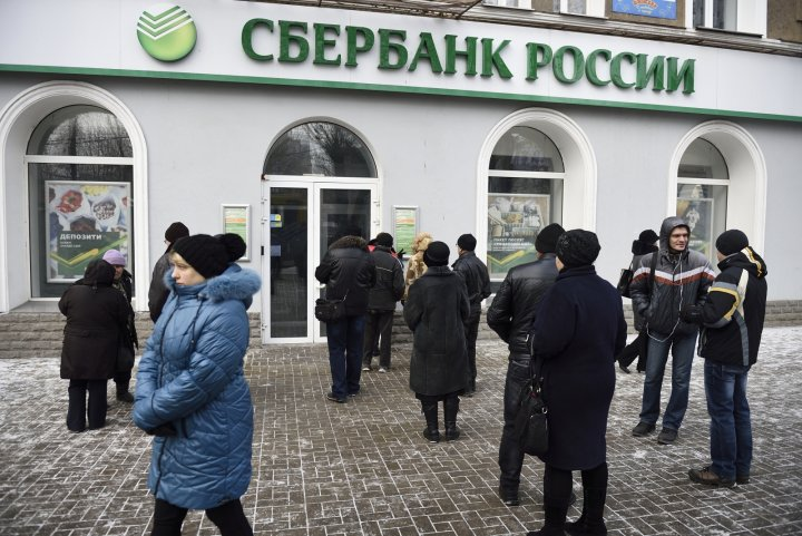 People wait in front of a closed bank on November 26, 2014 in the eastern Ukrainian city of Donetsk. No automated teller machines were working and most shops didn't accept payment by credit cards in Donetsk after Kiev asked for the suspension of banking