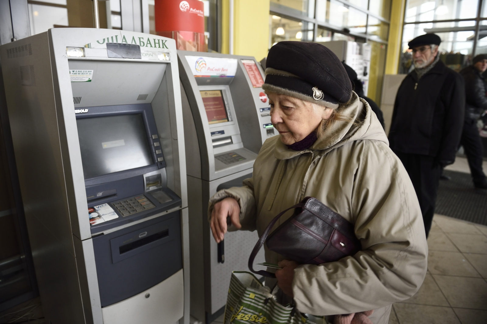 A woman walks in front of an ATM machine after she tried to get cash on November 26, 2014 in the eastern Ukrainian city of Donetsk.