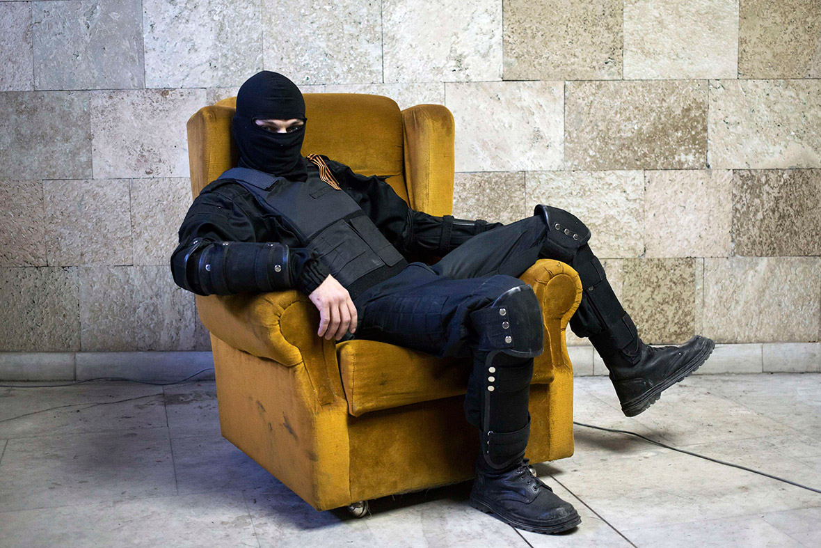 April 25, 2014: A masked pro-Russian protester sits on a chair as he poses for a picture inside a regional government building in Donetsk, eastern Ukraine