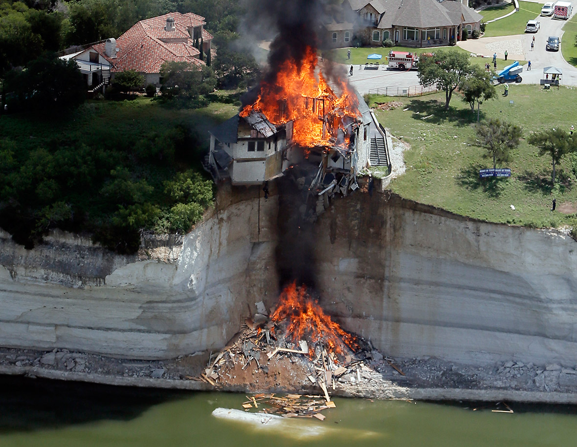 June 13, 2014: Smoke rises from a house days after part of the ground it was resting on collapsed into Lake Whitney, Texas