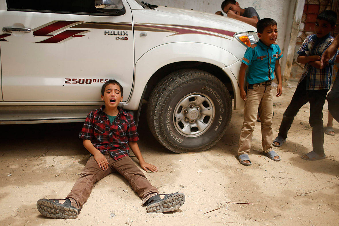 July 13, 2014: The son of one of the members of Tayseer Al-Batsh's family, who hospital officials said were killed in an Israeli air strike, mourns during their funeral in Gaza City