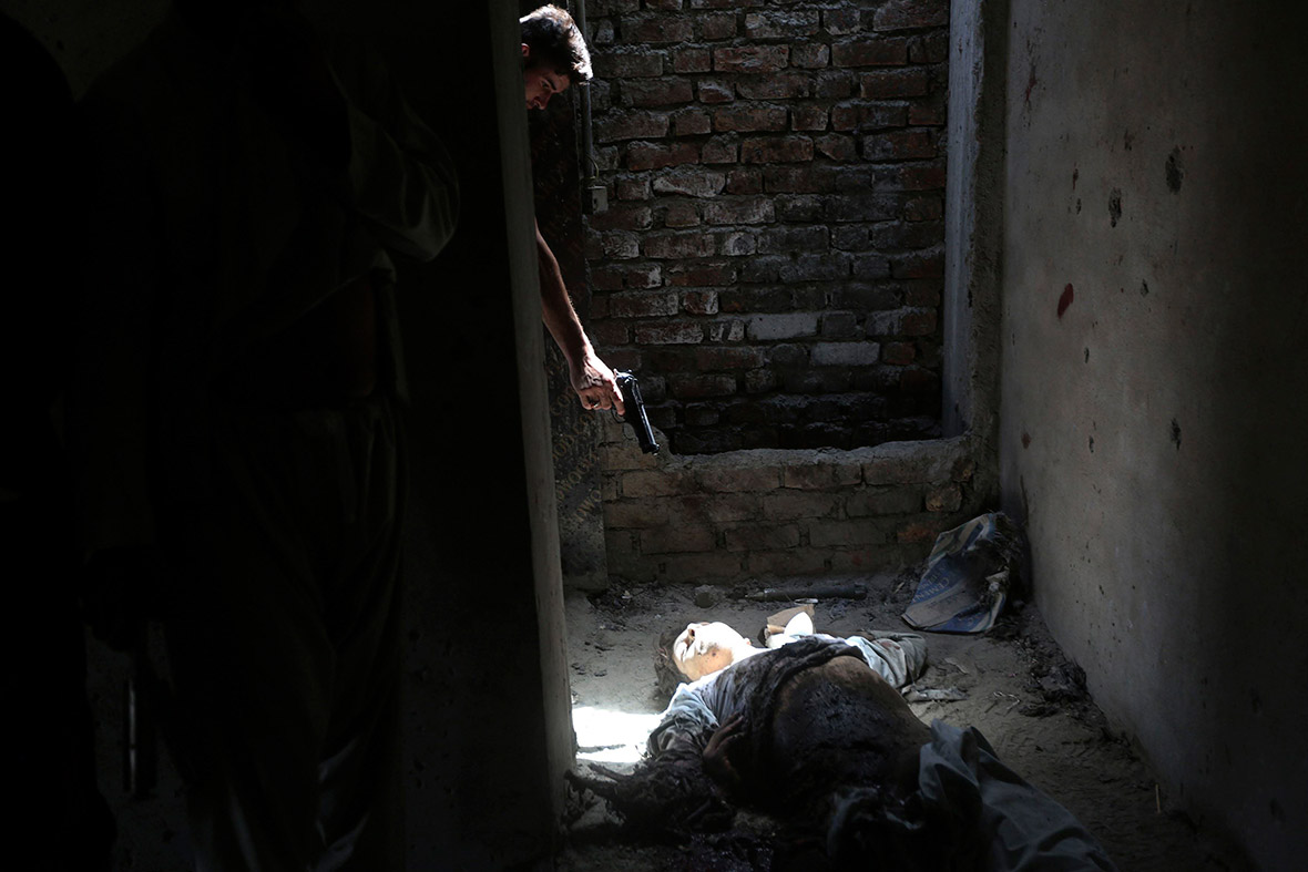 July 17, 2014:  A man points his weapon at the dead body of an unidentified militant, as a way of showing his hatred for insurgents, after an attack on Kabul airport