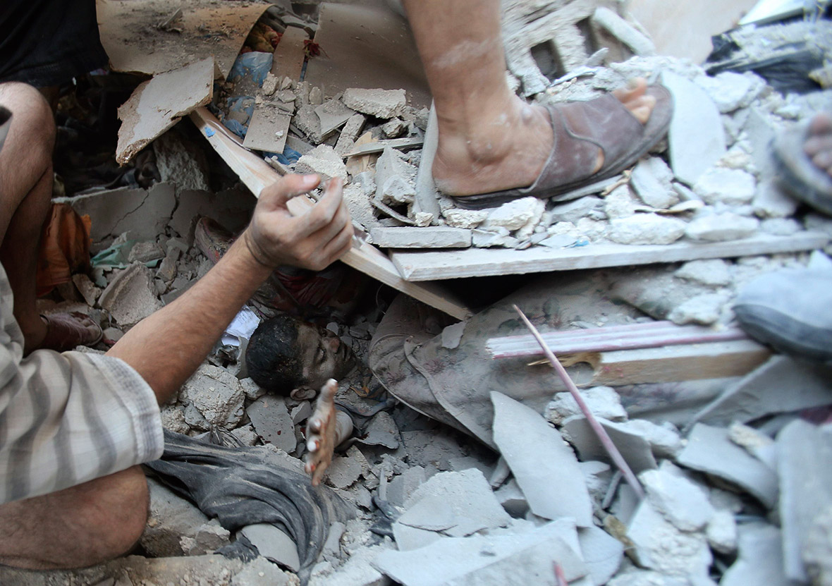 August 3, 2014: Palestinians rescue Mahmoud al-Ghol from under the rubble of a house in Rafah in the southern Gaza Strip