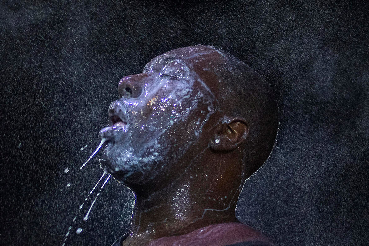 August 20, 2014: A man is doused with milk and sprayed with mist after being hit with an eye irritant by security forces in Ferguson, Missouri