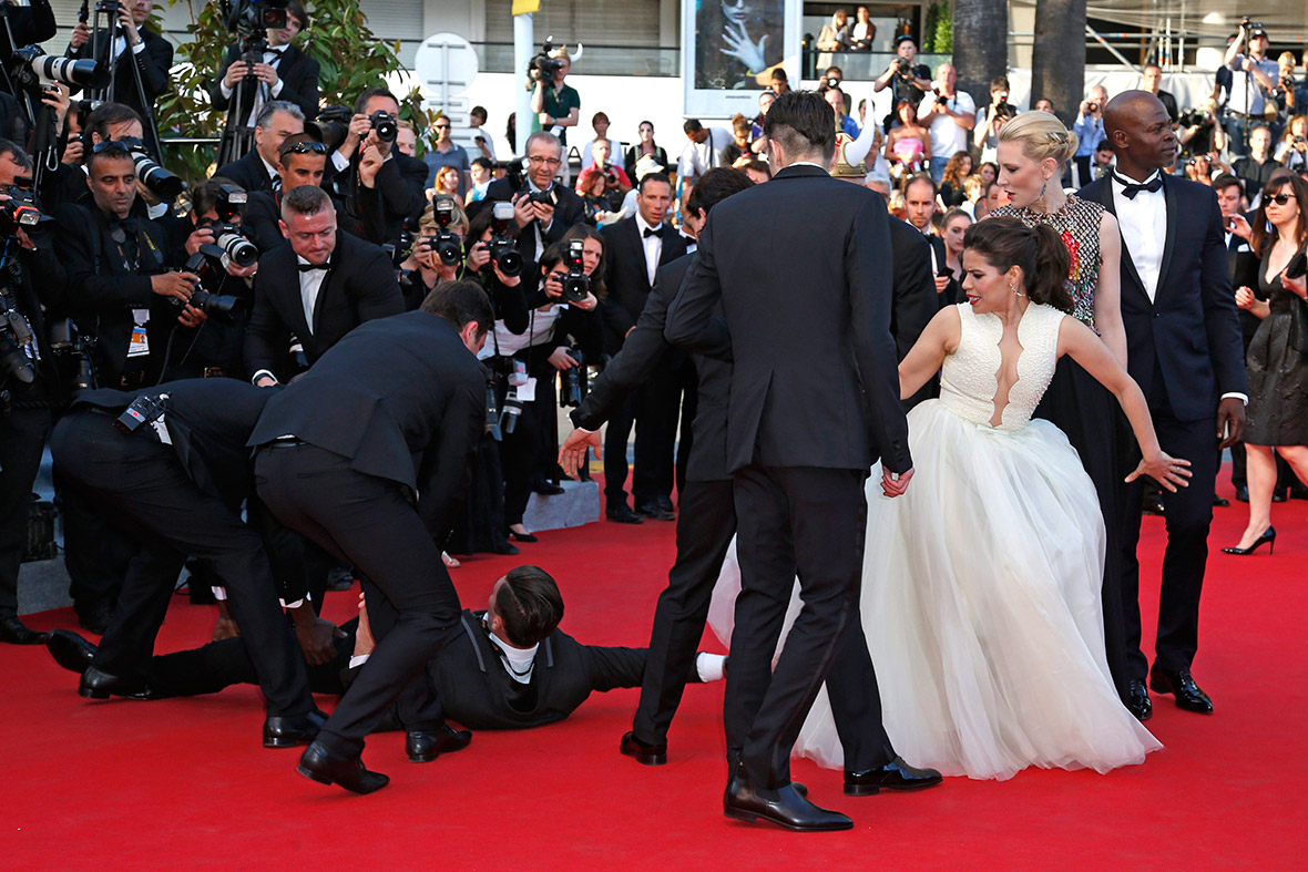 May 16, 2014: A man is arrested by security as he tries to slip under the dress of actress America Ferrera in Cannes