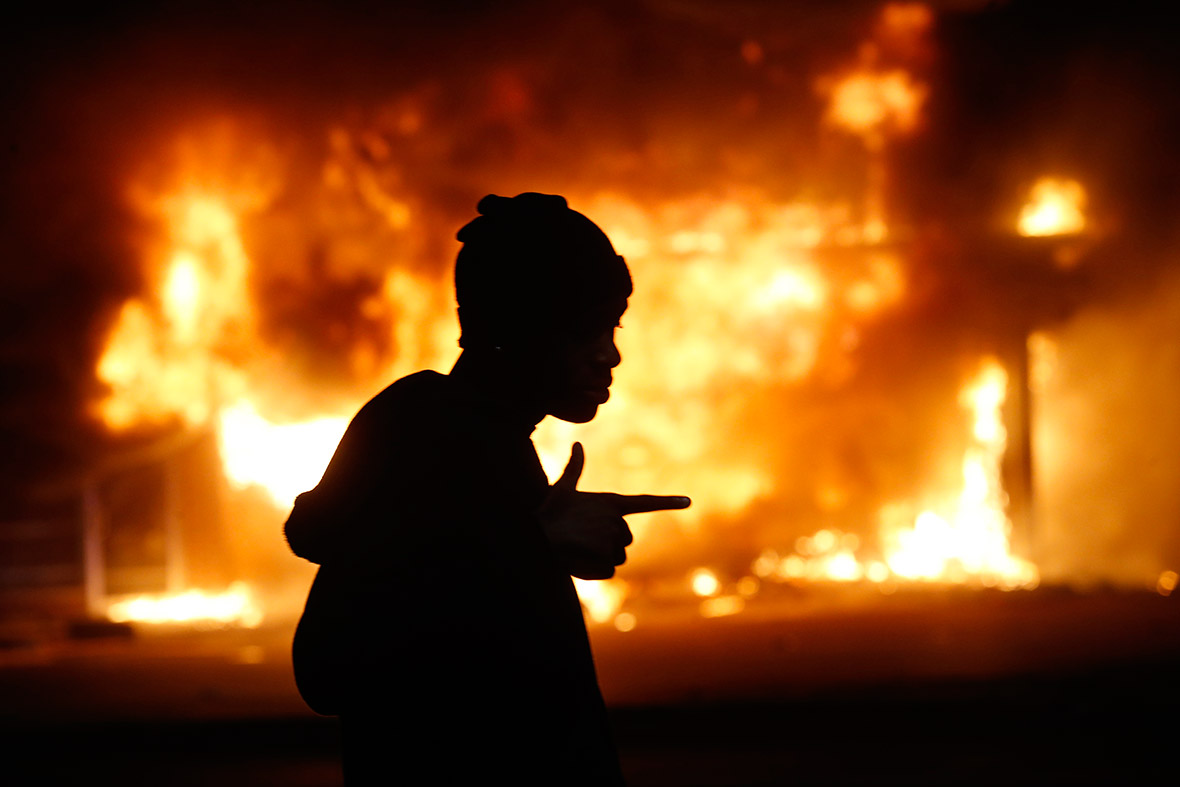 November 25, 2014: A man walks past a burning building during rioting after a grand jury returned no indictment in the shooting of Michael Brown in Ferguson, Missouri