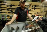 Metro Shooting Supplies\' employee Chris Cox speaks to a customer about the purchase of a 9mm handgun in Bridgeton, Missouri