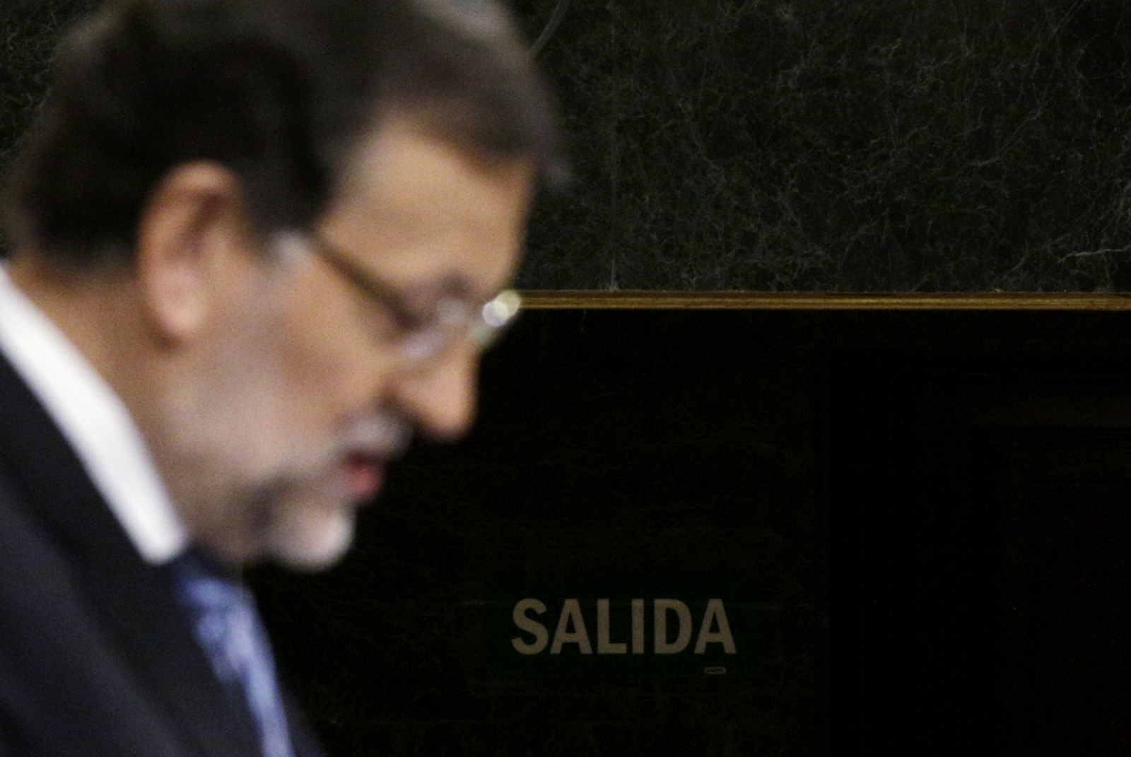 Spain's Prime Minister Mariano Rajoy delivers a speech presenting anti-corruption measures in front of an exit sign at Spanish parliament in Madrid, November 27, 2014.
