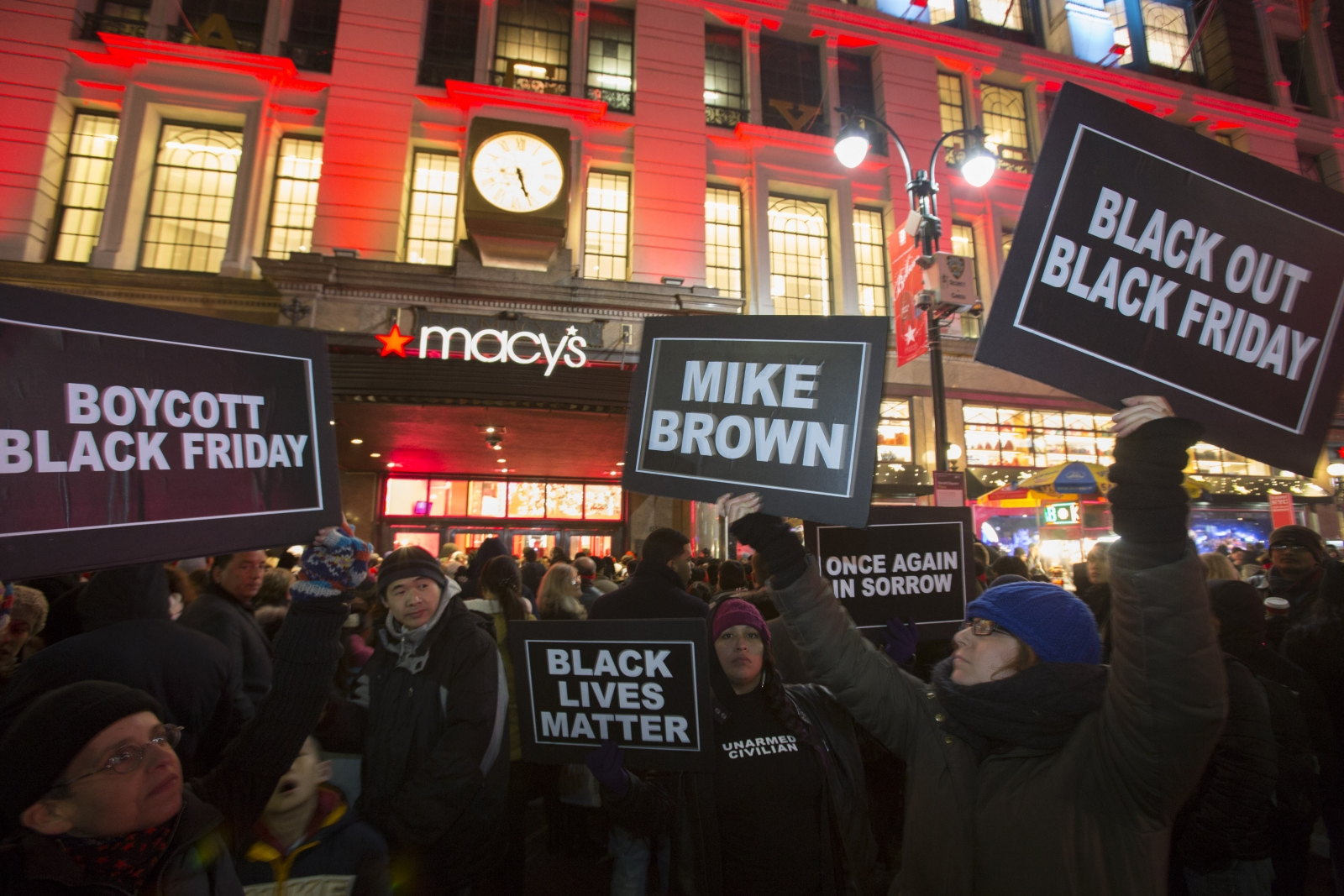 Protesters hold signs aloft outside Macy's before the kick off of Black Friday sales in New York November 27, 2014. Select stores opened Thursday to kick off the Black Friday sales, with the Friday after Thanksgiving typically being the busiest shopping