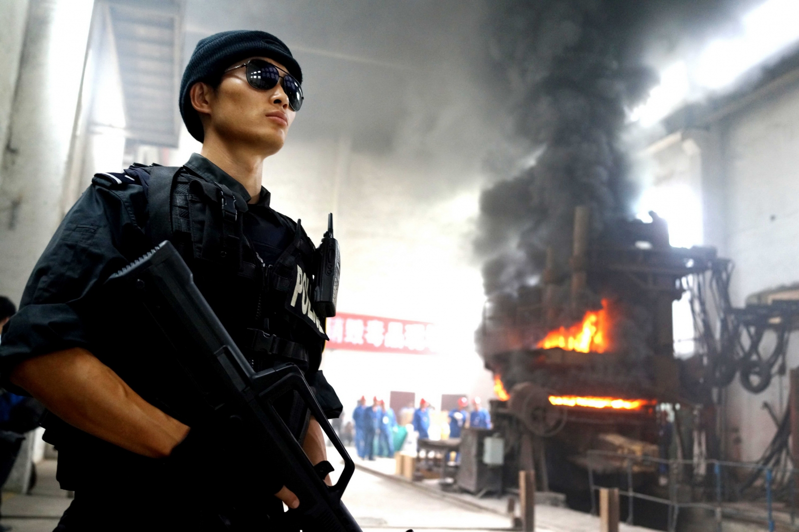 Chinese police stand guard as a drugs factory in Guizhou province is destroyed.