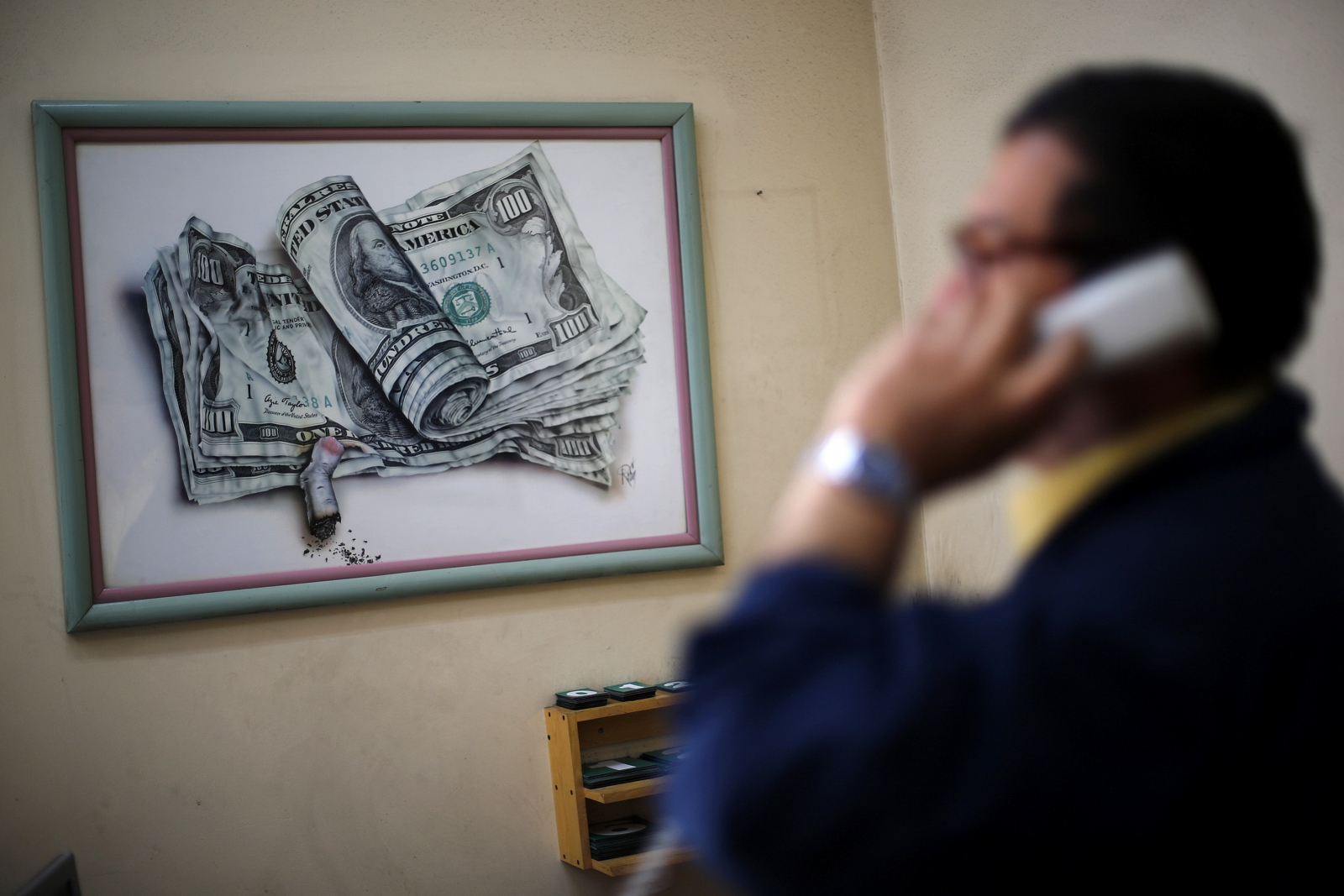 A man talks on the telephone, in front of a caricature of dollar bills