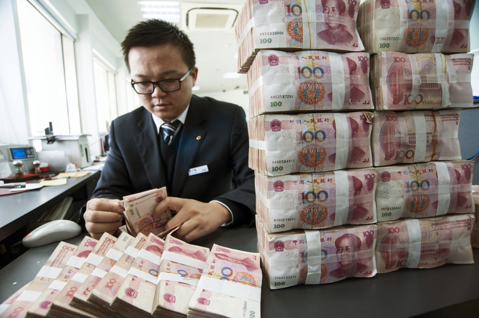 A clerk counts Chinese 100 yuan banknotes at a branch of China Construction Bank