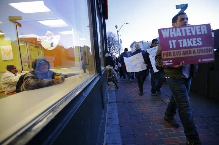 Fast food workers and their supporters calling for a $15 minimum wage walk past a men sitting in a McDonalds restaurant in Chelsea, Massachusetts December 4, 2014