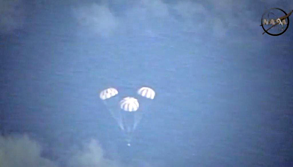 Images from Nasa's Ikhana unmanned aerial drone show the Orion crew module landing in the Pacific Ocean