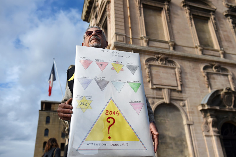 A protester holds a sign comparing the Homeless identity cards introduced in Marseille with the yellow Star of David Jews were forced to wear in Nazi Germany. (Anne-Christine Poujoulat/AFP)