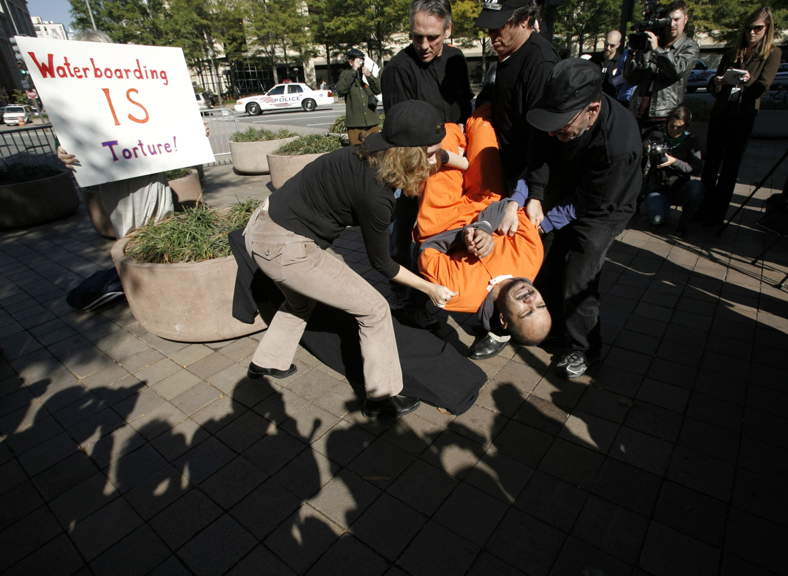 Demonstrator Maboud Ebrahimzadeh is lowered onto the board during a simulation of waterboarding outside the Justice Departement in Washington