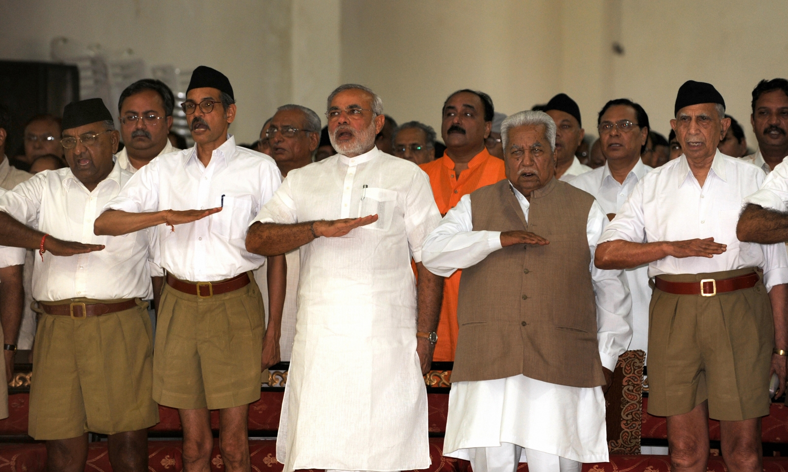 Gujarat state Chief Minister Narendra Modi (3rd L) and former chief minister Keshubhai Patel (2nd R, front) gesture as they attend a Rashtriya Swayamsevak Sangh (RSS) gathering at the Tria Mandir in Adalaj, some 20 kms from Ahmedabad