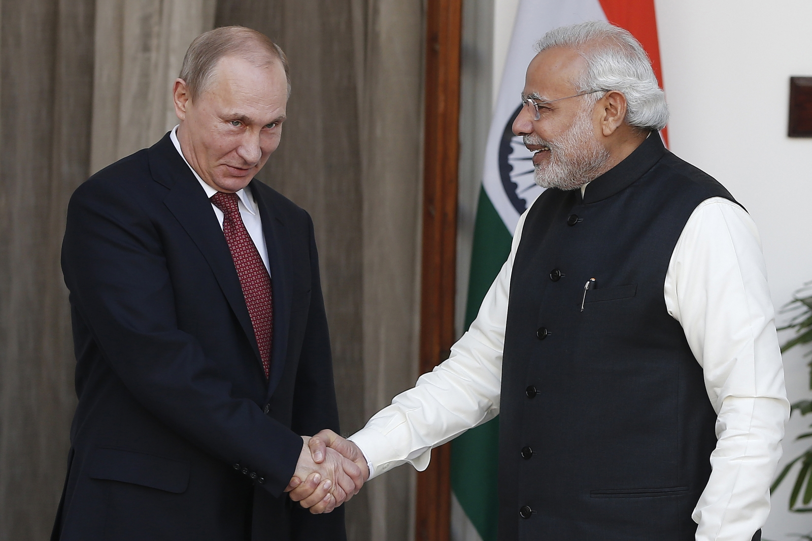 Russian President Vladimir Putin (L) shakes hands with India's Prime Minister Narendra Modi during a photo opportunity ahead of their meeting at Hyderabad House in New Delhi