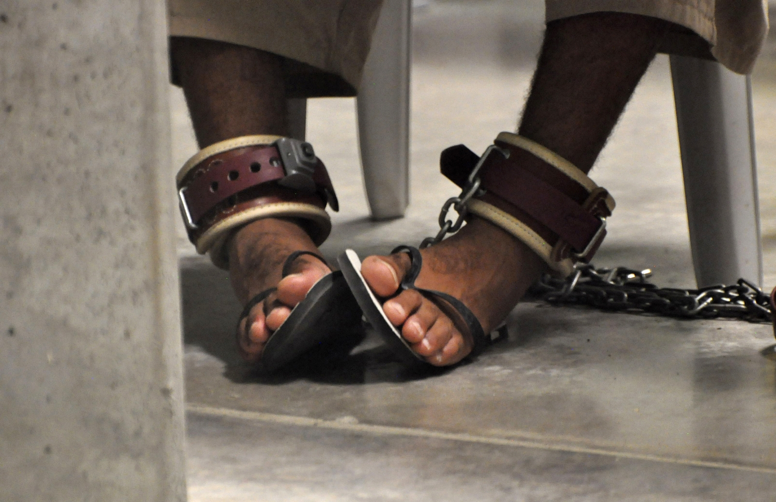 In this photo, reviewed by a U.S. Department of Defense official, a Guantanamo detainee's feet are shackled to the floor as he attends a