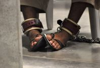 In this photo, reviewed by a U.S. Department of Defense official, a Guantanamo detainee\'s feet are shackled to the floor as he attends a