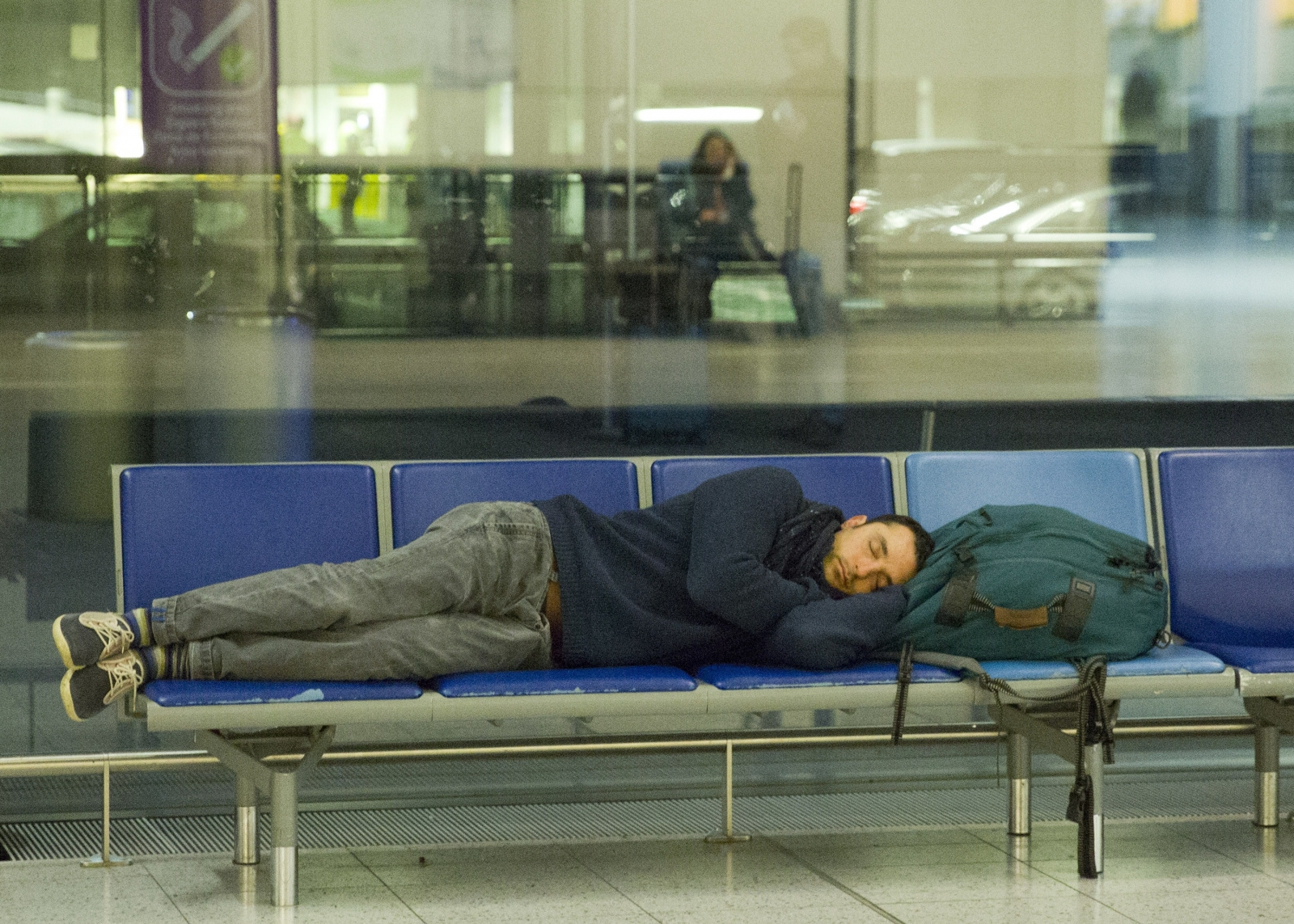 A man gets some rest at Gatwick, after an air traffic control systems failure caused traffic chaos. (Getty)