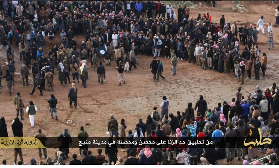 Crowd watch a man and a woman being stoned to death for adultery in Manbij, Syria.