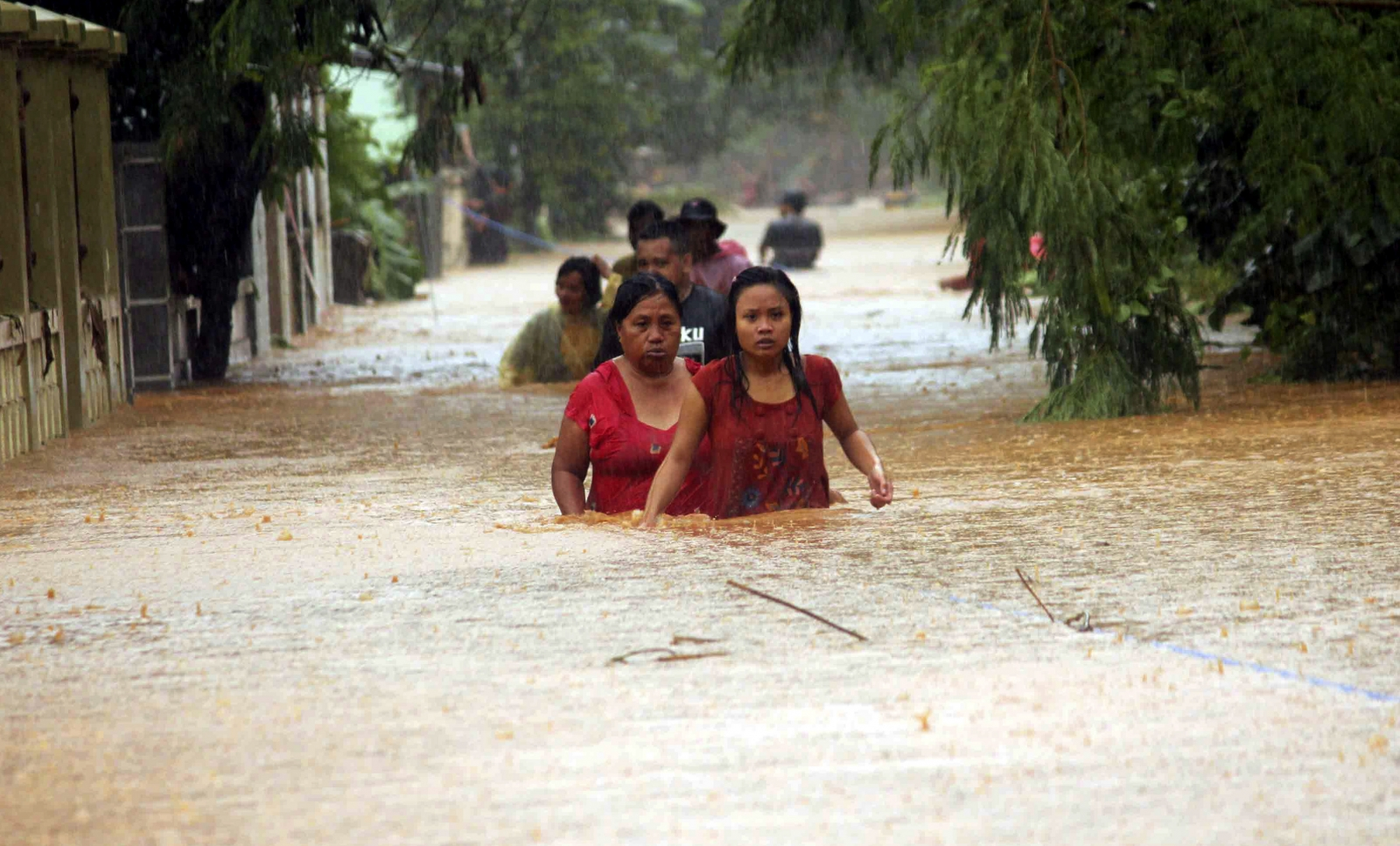 Residents walk through a flooded village in Indonesia
