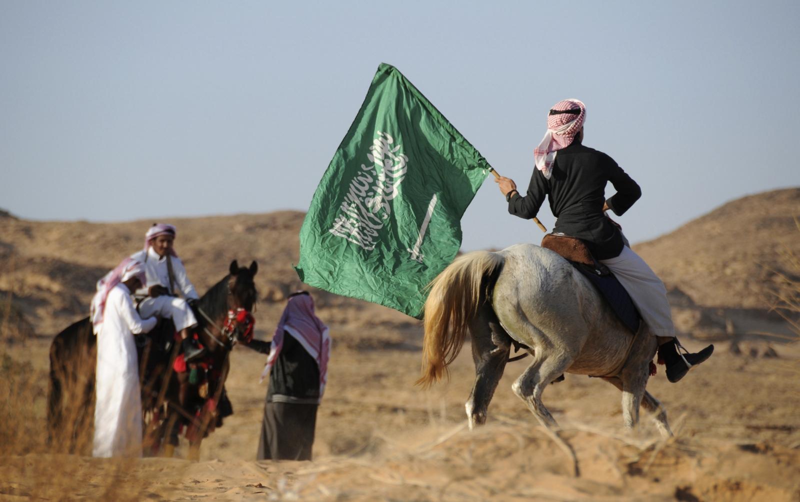 A Saudi man riding a horse waves a national flag