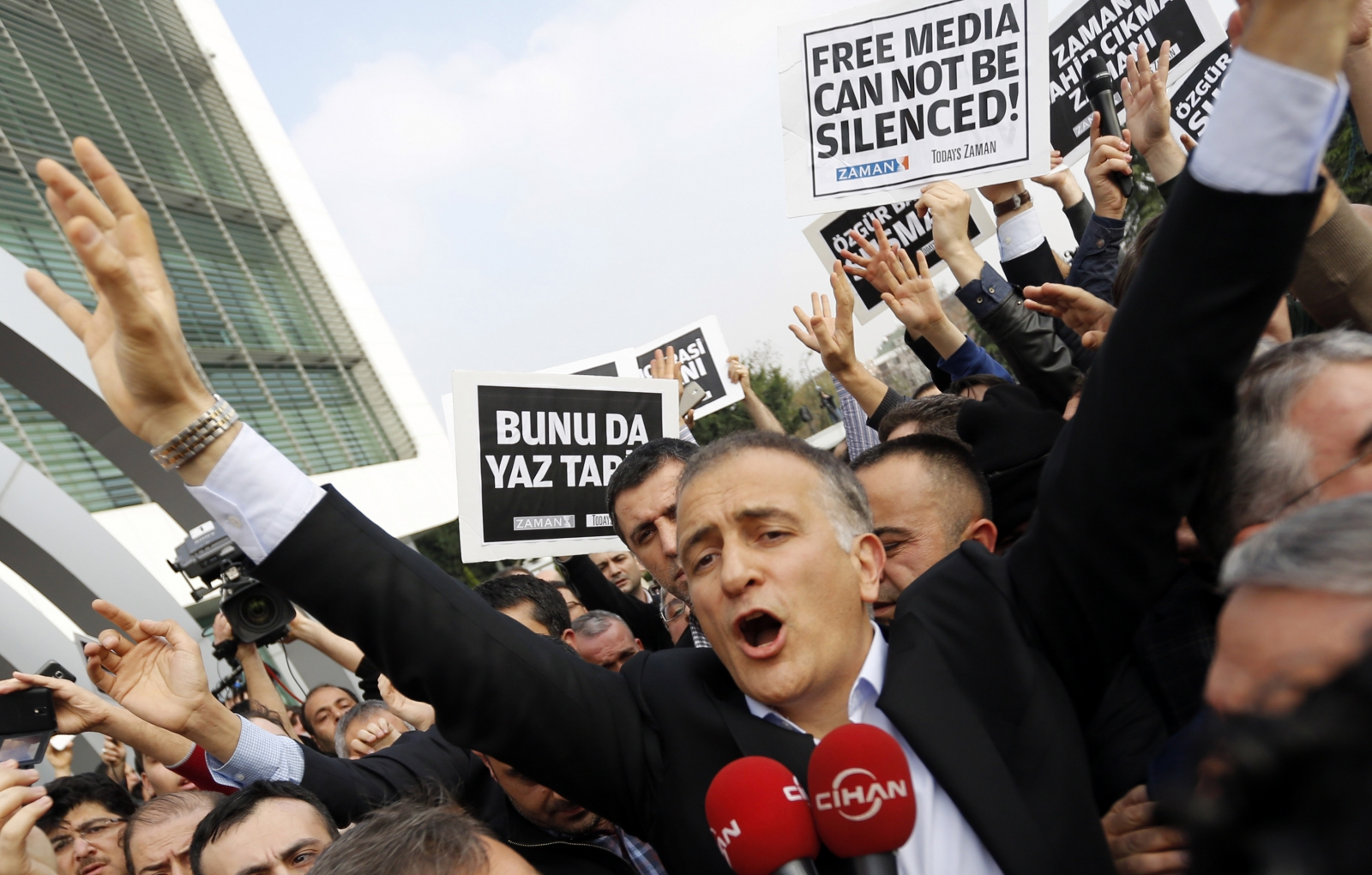 Zaman editor-in-chief Ekrem Dumanli, surrounded by his colleagues and plainclothes police officers (C), reacts as he leaves the headquarters of Zaman daily newspaper in Istanbul