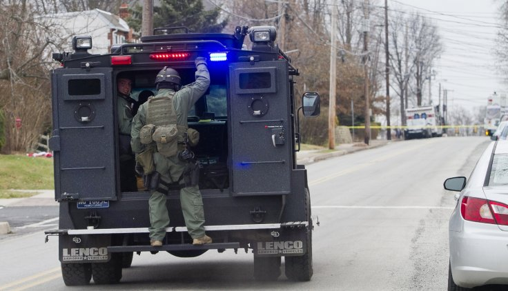 Police SWAT teams search outside a home in a suburb of Philadelphia where a suspect in five killings was believed to be barricaded in Souderton, Pennsylvania