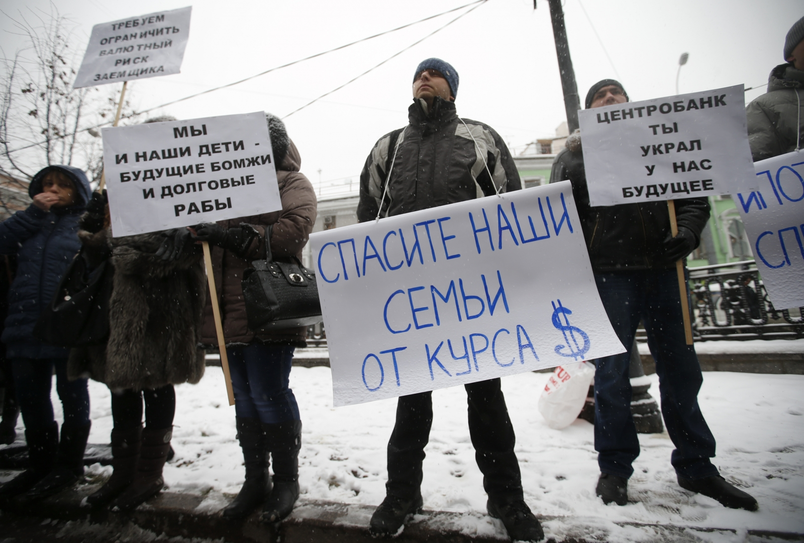 Protesters hold placards during a picket in central Moscow, December 12, 2014. According to local media, the people, who took mortgages in foreign currencies, now face larger risks due to the weakening of the rouble. The placards read,