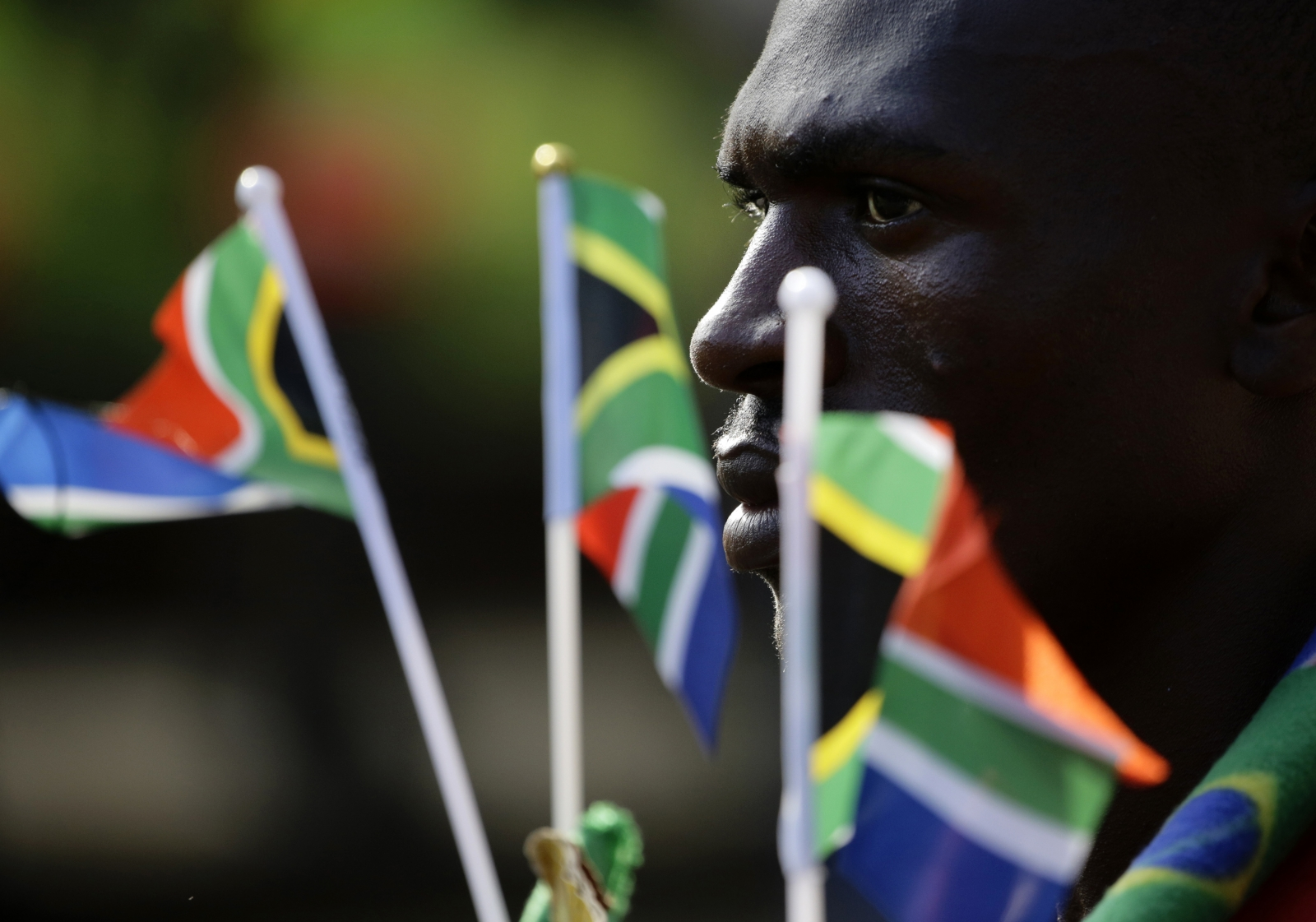 Man holds South African national flags as he waits to view the body of former South African President Nelson Mandela.