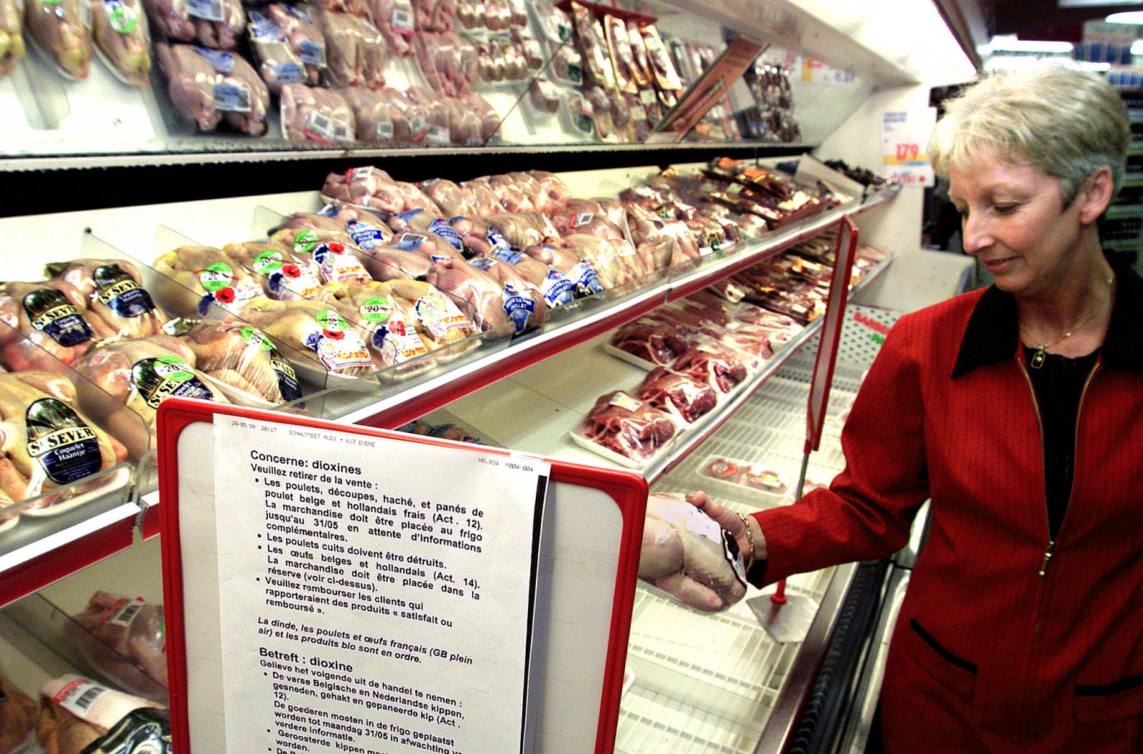 A woman examines a chicken in a Brussels supermarket June 1.