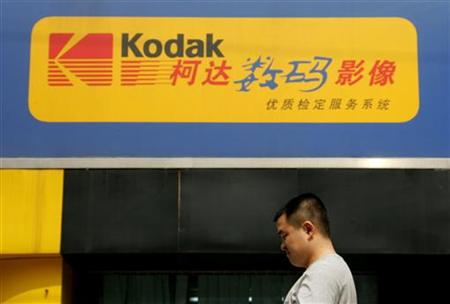 Chinese man walks past a Kodak digital express shop in Beijing.