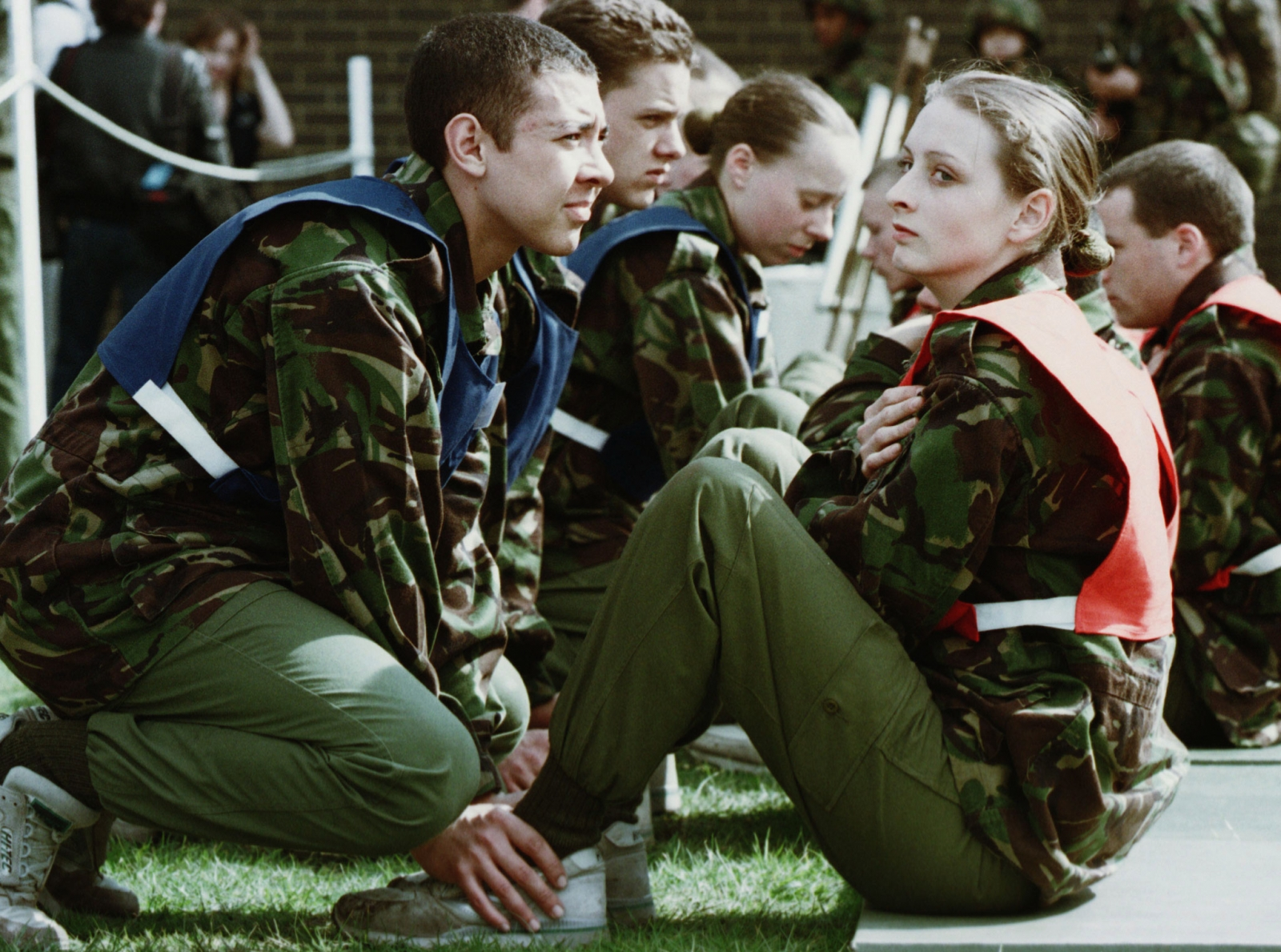 A female recruit does situps while a male recruit holds her ankles during the new equal opportunities physical tests for the British Army in Pirbright