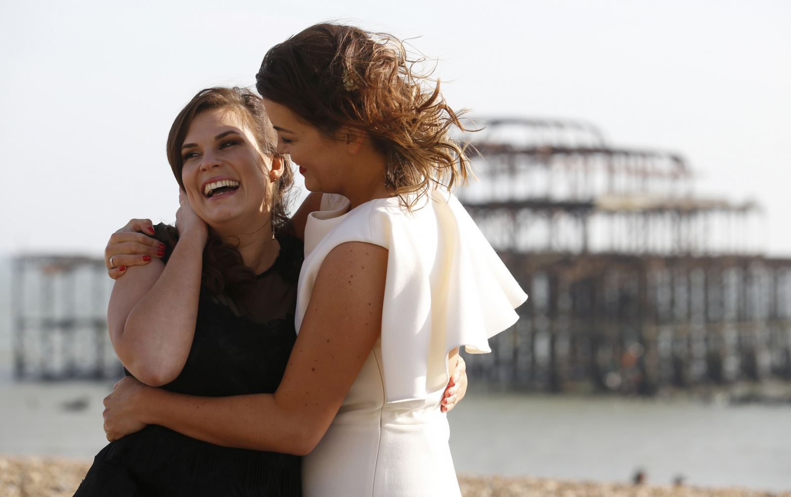 Lesbian couple Sarah Keith (R) and Emma Powell pose for photographs after their same-sex wedding at the Claremont Hotel in Brighton, southern England
