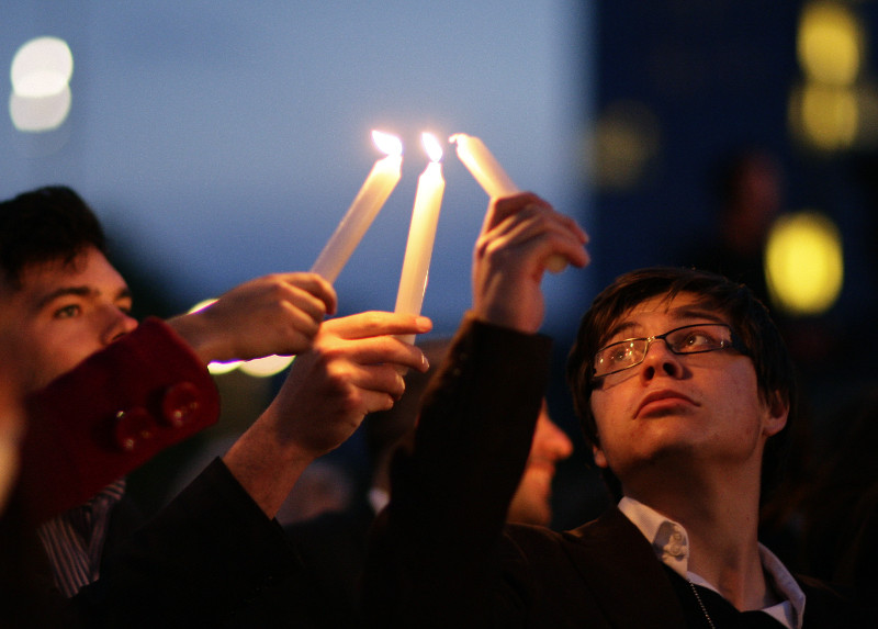 Observers light candles during an event to commemorate the Holocaust