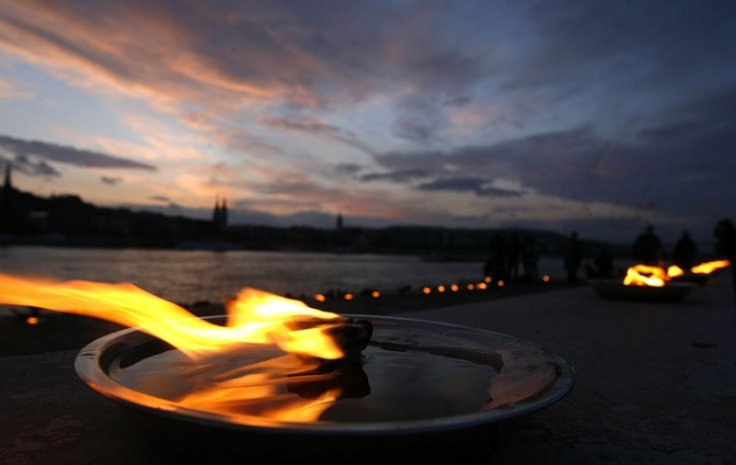 Candles burn at a memorial of shoes in remembrance of Holocaust victims