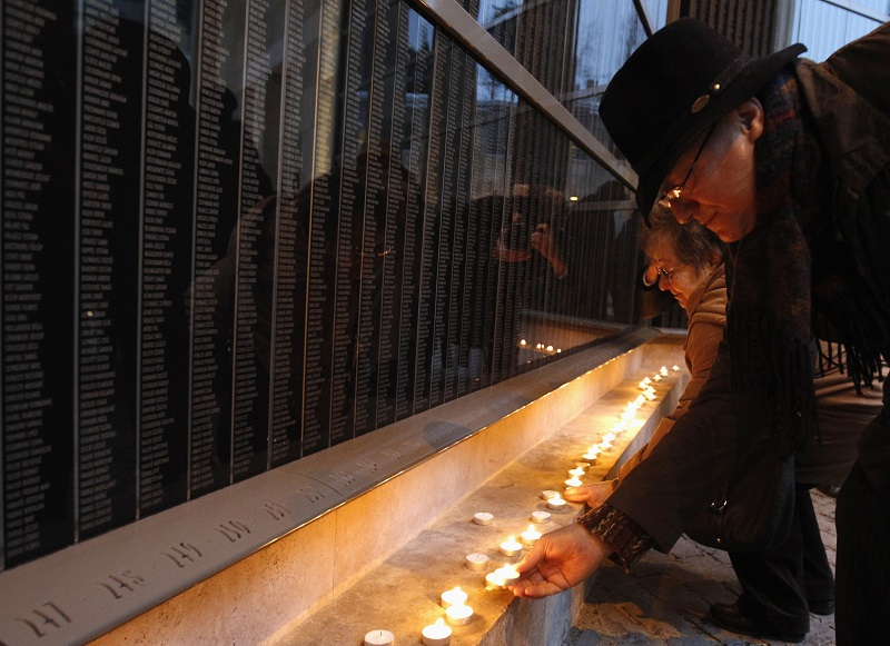 People light candles in front of a wall containing the names of Holocaust victims