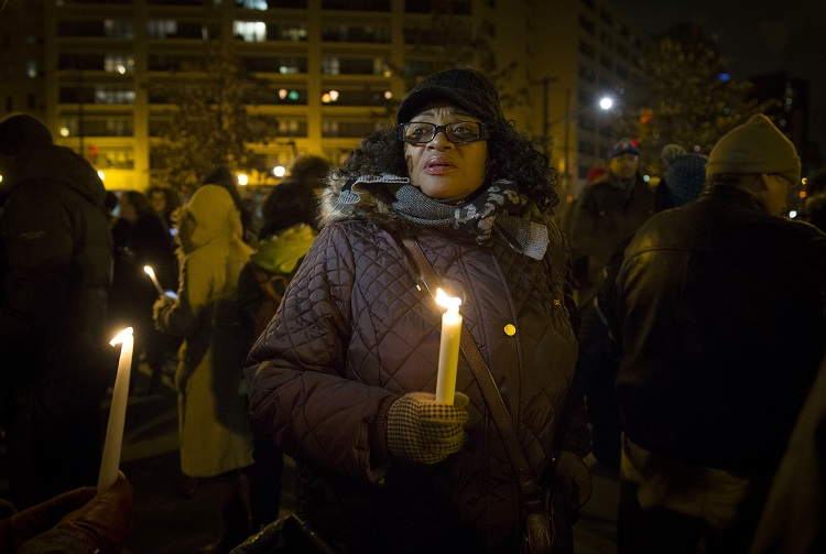 A woman holds a candle as demonstrators gather in Central Park in Harlem, New York City, for a candlelight vigil and march for justice December 21, 2014.