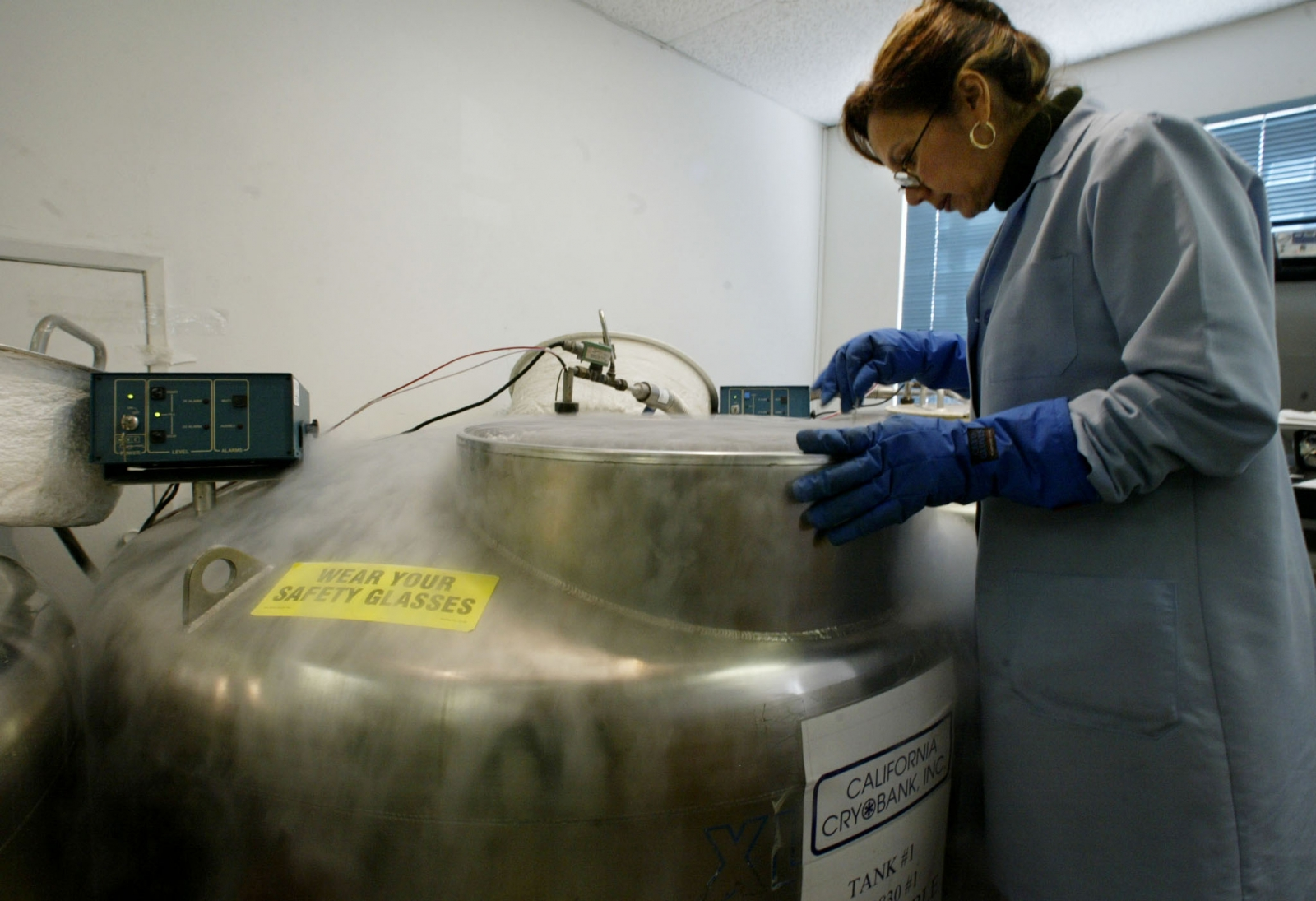 A scientist in California stands over a cryogenic tank. (Reuters)
