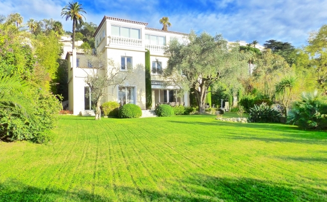 The villa is surrounded by gardens. (Fine and Country)