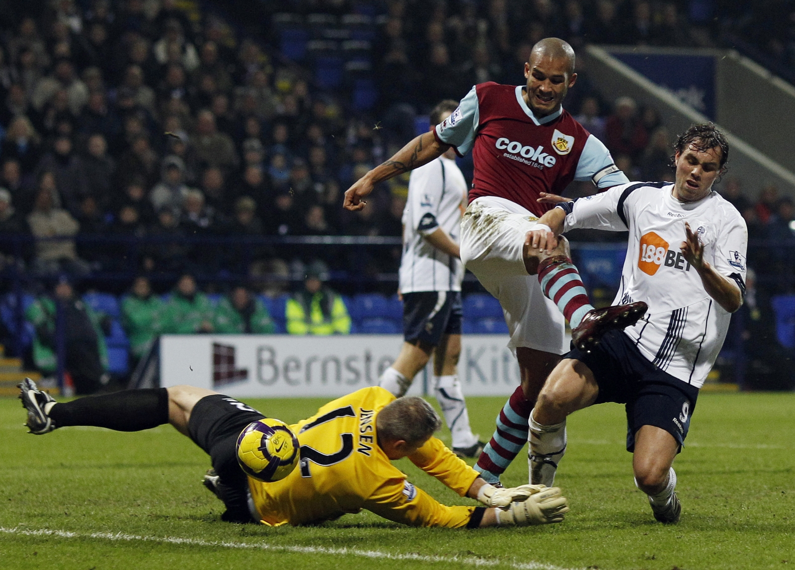 Bolton Wanderers' Johan Elmander is challenged by Burnley's Brian Jensen (L) and Clark Carlisle (C) during their English Premier League soccer match at the Reebok stadium in Bolton