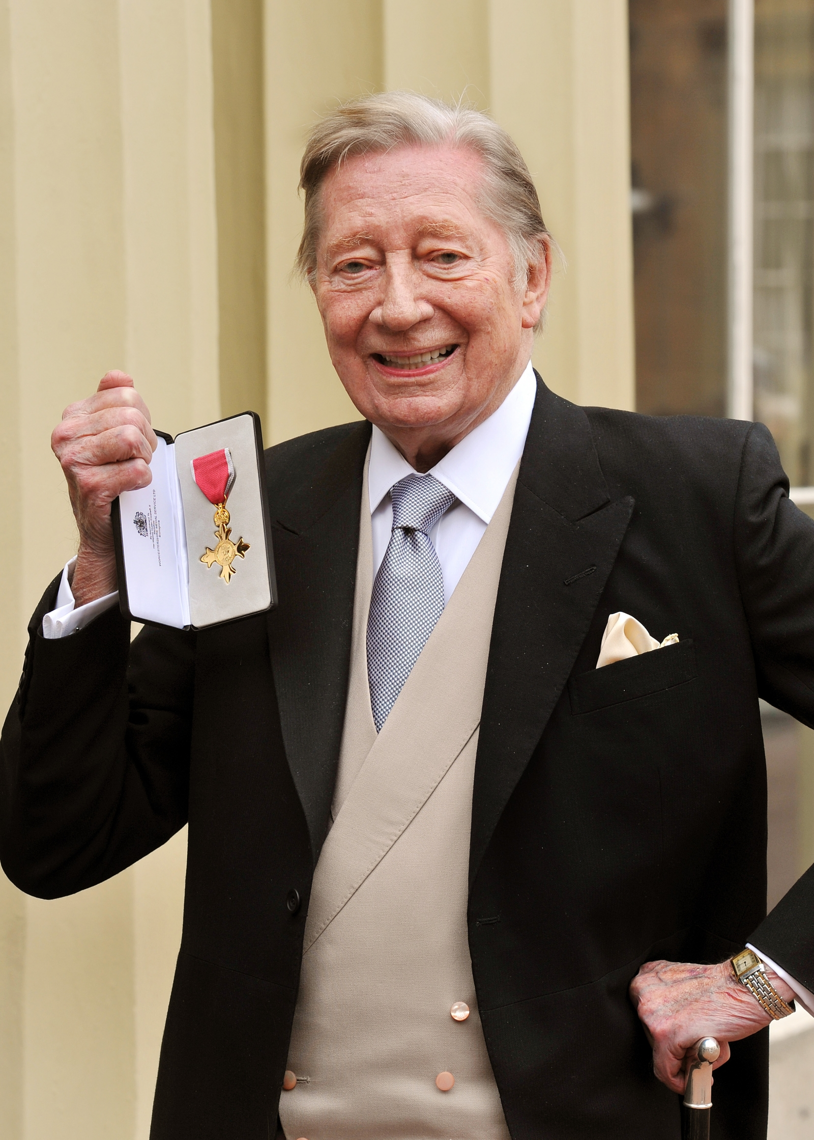 Jeremy Lloyd holds his Officer of the British Empire (OBE) medal after it was presented to him by Queen Elizabeth II at the Investiture Ceremony at Buckingham Palace on February 13, 2012