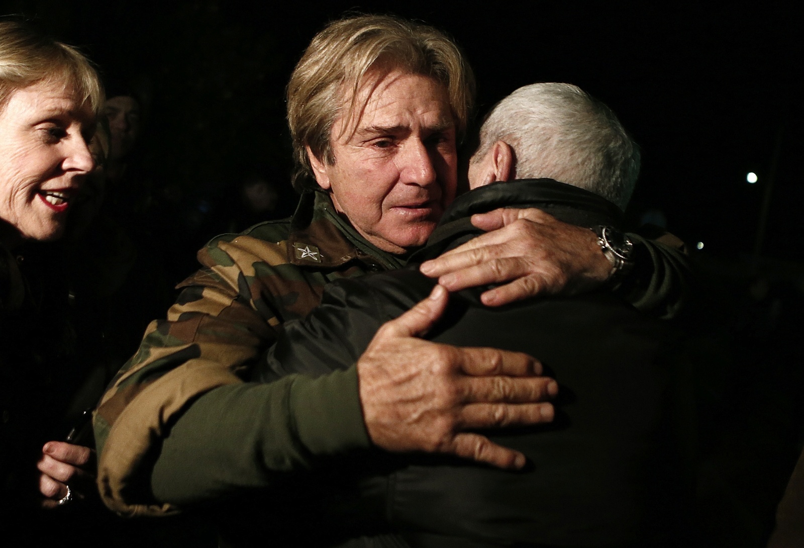 Andreas Tolaros, who was rescued from the Norman Atlantic ferry, hugs a friend after arriving at the Elefsina air-base near Athens